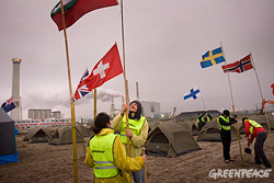 Action on the Maasvlakte: activists plant 18 flags, one for each nationality at the camp