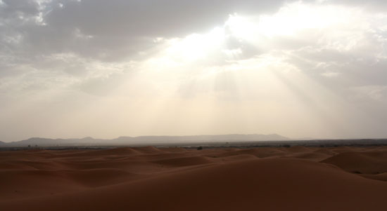 The image shows the sun shining through the clouds on the Sahara desert in Morocco. Photo by: GETA.80.