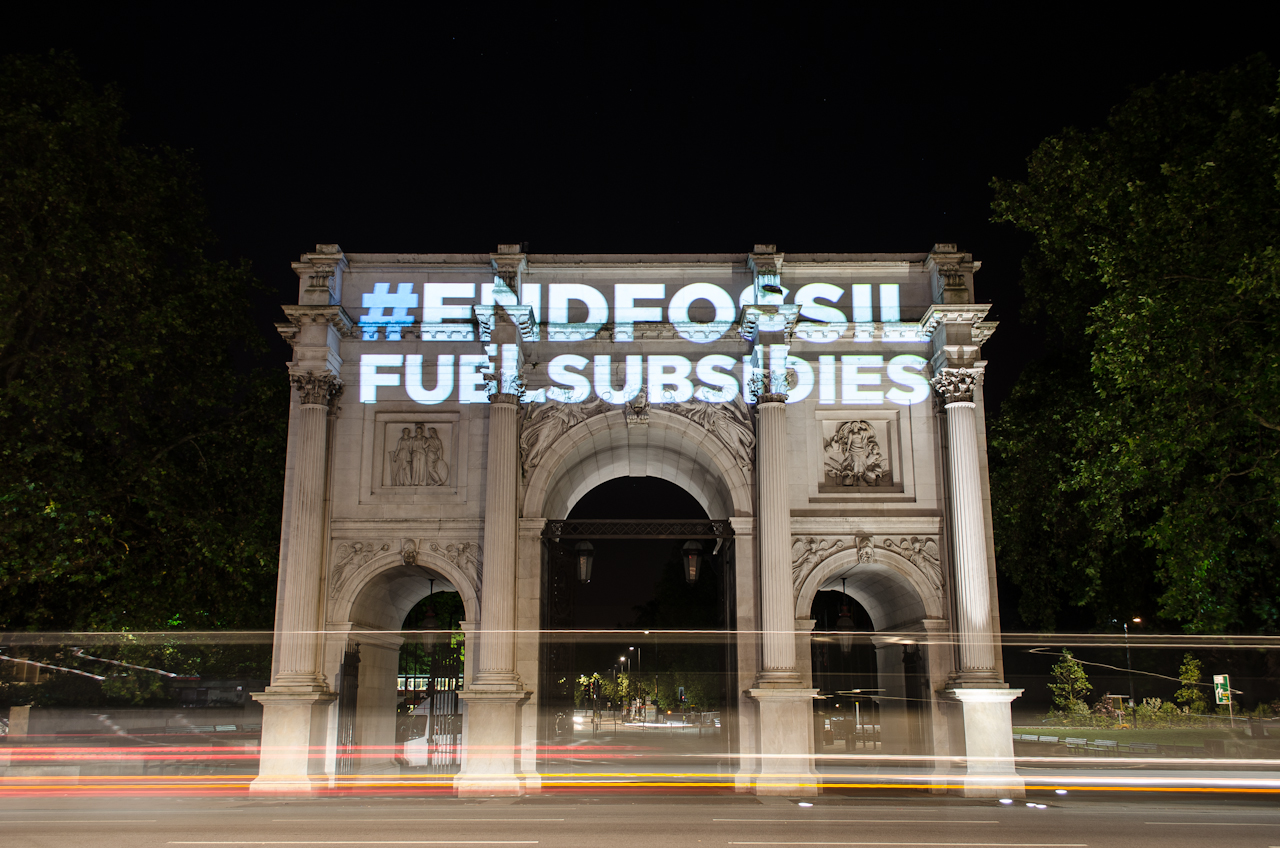 The #EndFossilFuelSubsidies hashtag is seen here being projected at the Marble Arch in London. Photo: Stephen Brown